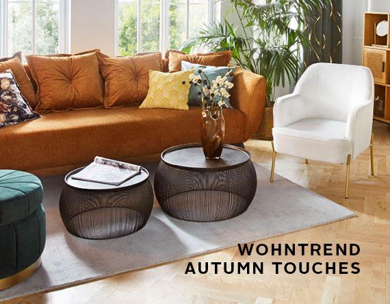 ockerfarbige Couch, Beistelltische, weißer Sessel, Kissen, Deko