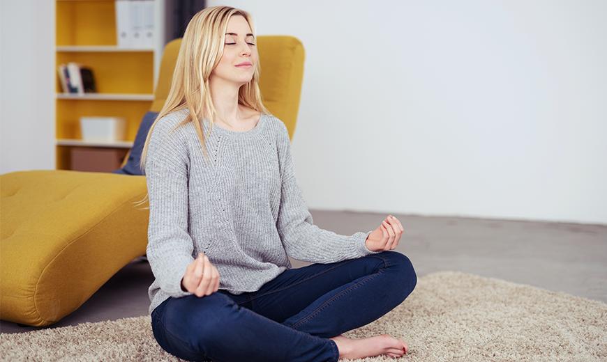 Meditierende Frau in der Wohnung