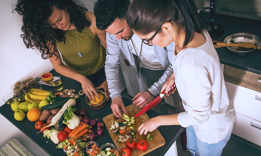Freunde kochen gemeinsam mit Obst und Gemüse.