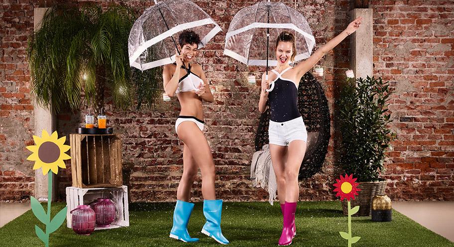 2 junge Damen tanzen mit Regenschirm und bunten Stiefeln im Regen